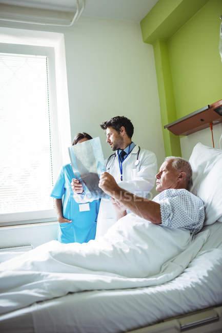 Médico e enfermeiro interagindo sobre o relatório de raios-X com o paciente no hospital — Fotografia de Stock