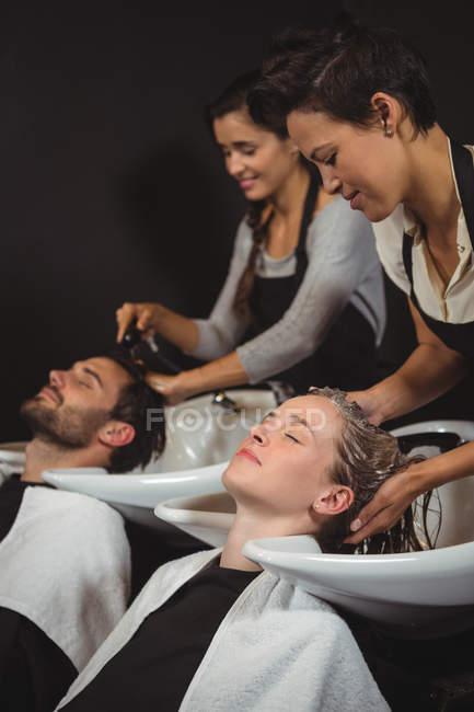 Clientes recebendo sua lavagem de cabelo no salão — Fotografia de Stock