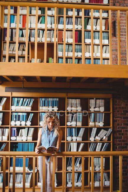 Belle femme lecture livre dans la bibliothèque — Photo de stock