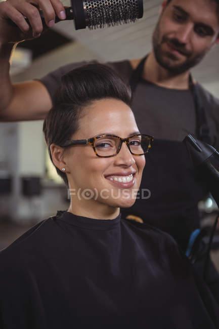Портрет улыбающейся женщины, высушивающей волосы феном в парикмахерской — стоковое фото