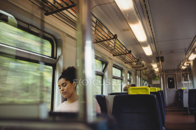 Beautiful woman napping while sitting in train — Stock Photo