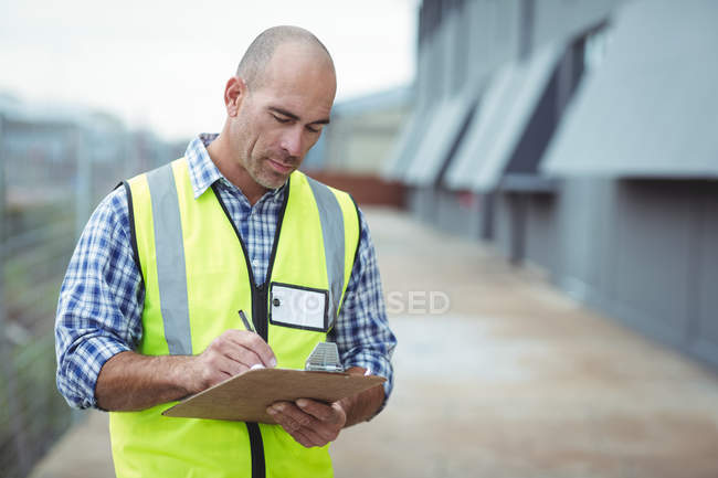 Construction worker writing on clipboard outside office — Stock Photo
