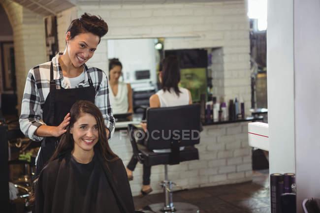 Coiffeuse souriante travaillant sur le client dans le salon de coiffure — Photo de stock