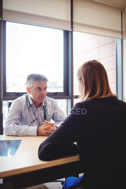 Врач за столом разговаривает с пациентом в больнице — стоковое фото