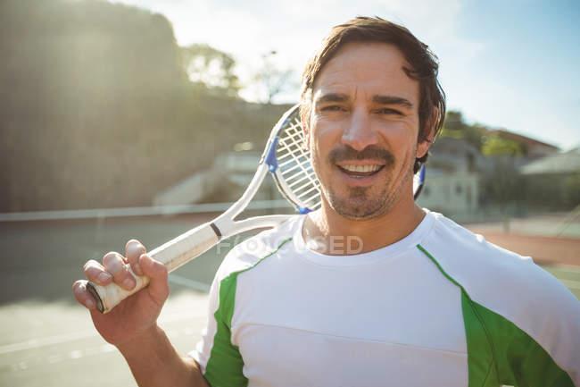 Feliz hombre de pie en la corte con raqueta de tenis - foto de stock