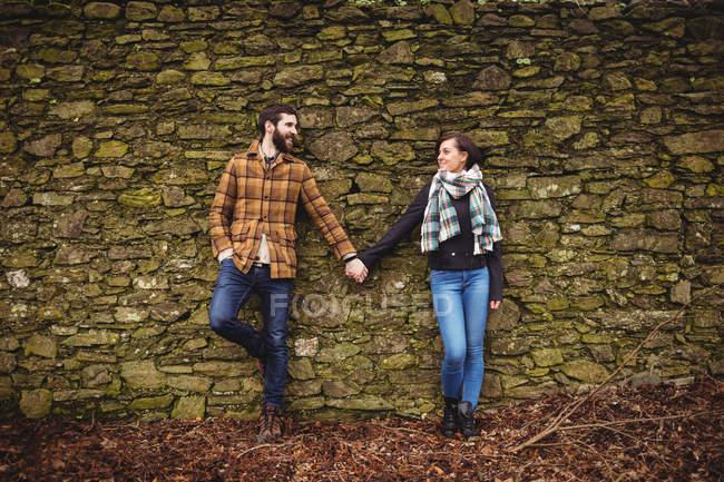 Щаслива пара притулившись кам'яною стіною — стокове фото