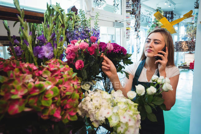Female Florist Talking On Mobile Phone While Arranging
