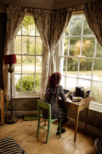 Rear view of woman using tablet computer by window at home — Stock Photo