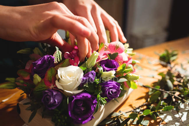 Close-up of female florist preparing a flower bouquet at her flower shop — Stock Photo