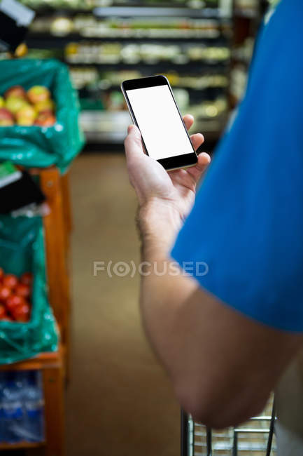 Cropped image of Man using mobile phone while shopping in supermarket — Stock Photo