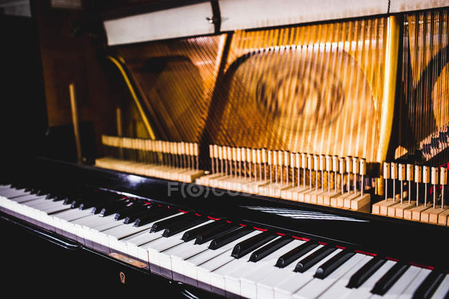 Vintage wooden piano with classic keyboard at antique workshop — Stock Photo