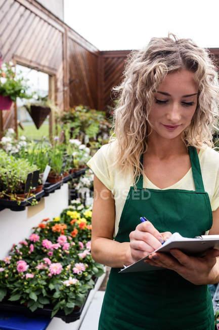 Жіночий флорист дати з буфера обміну в садовому центрі — стокове фото
