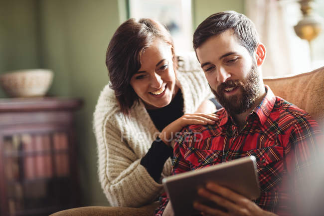 Couple using digital tablet in living room at home — Stock Photo