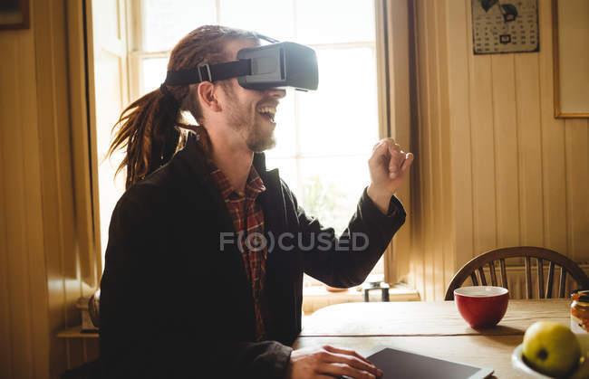Счастливый молодой человек использует симулятор виртуальной реальности дома — стоковое фото