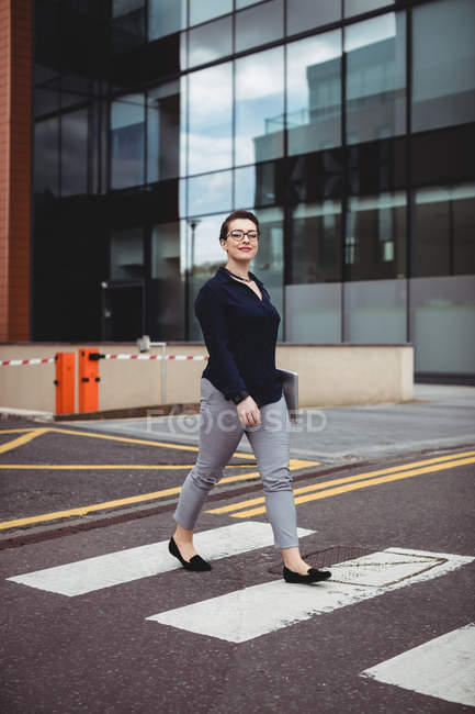 Full length portrait of confident businesswoman walking on road — Stock Photo