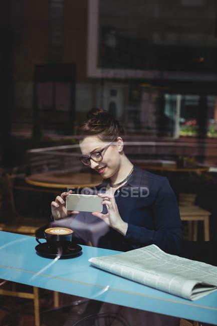 Усміхаючись молода жінка фотографує в кафе видно через скло — стокове фото