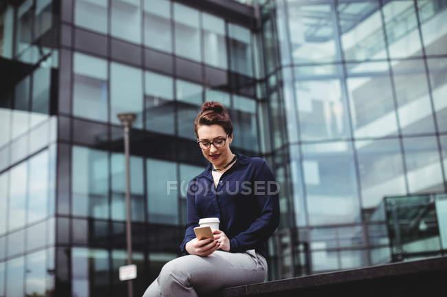 Mujer joven usando teléfono móvil contra edificio de oficinas moderno - foto de stock