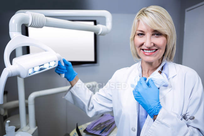 Portrait of smiling dentist at dental clinic — Stock Photo