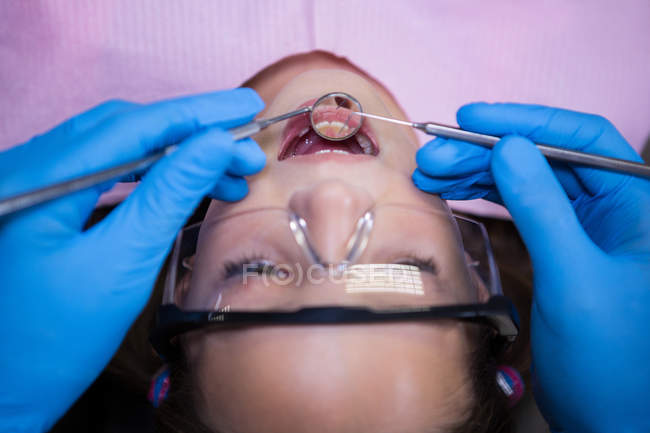 Dentist examining young patient with tools at dental clinic — Stock Photo