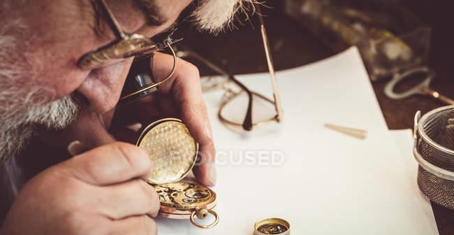 Горолог ремонтирует карманные часы в мастерской — стоковое фото