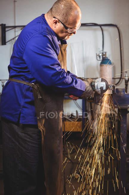 Сварщик распиливания металла с электрическим инструментом в мастерской — стоковое фото