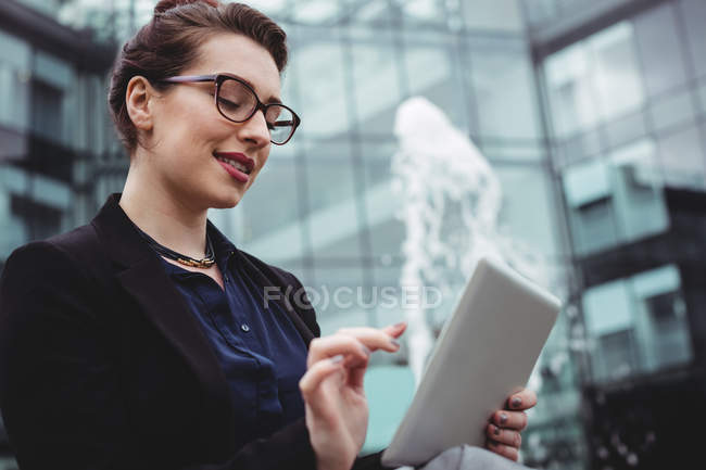 Smiling businesswoman using digital tablet outside office building — Stock Photo
