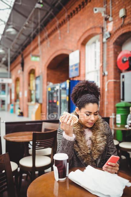 Donna che usa il telefono mentre è seduta al ristorante della stazione ferroviaria — Foto stock