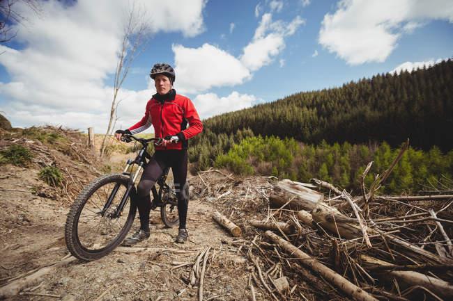 Вид спереди байкера с велосипедом на горе на фоне неба — стоковое фото