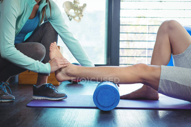 Cropped image of Female physiotherapist giving physical therapy to leg of male patient in clinic — Stock Photo