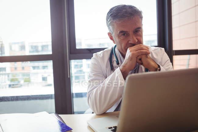 Portrait du médecin avec stéthoscope assis au bureau à l'hôpital — Photo de stock