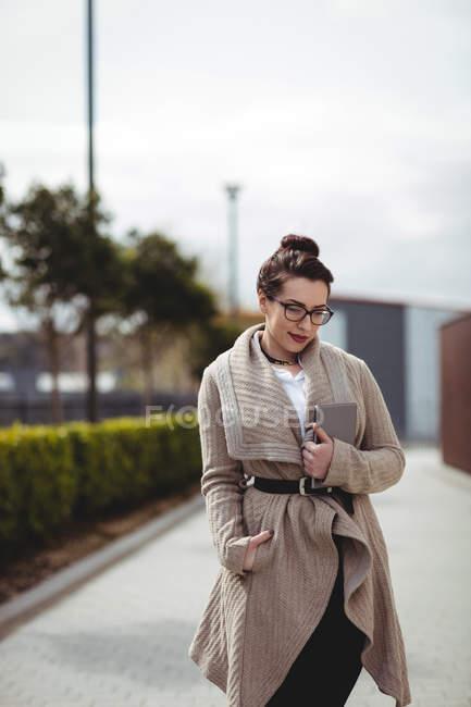 Nachdenkliche junge Frau mit digitalem Tablet steht auf Fußweg — Stockfoto