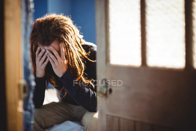 Грустно битник человек, сидя на кровати у себя дома — стоковое фото