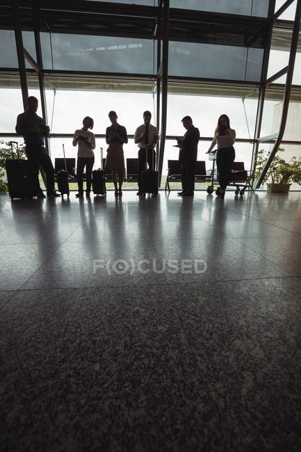 Business people using mobile phones in waiting area at airport terminal — Stock Photo