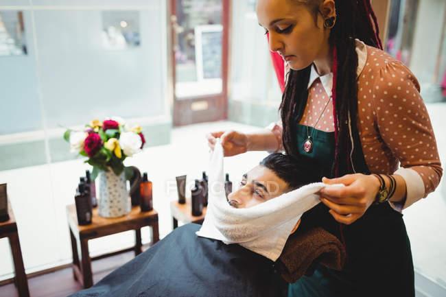 Barbier appliquer une serviette chaude sur le visage du client dans le salon de coiffure — Photo de stock