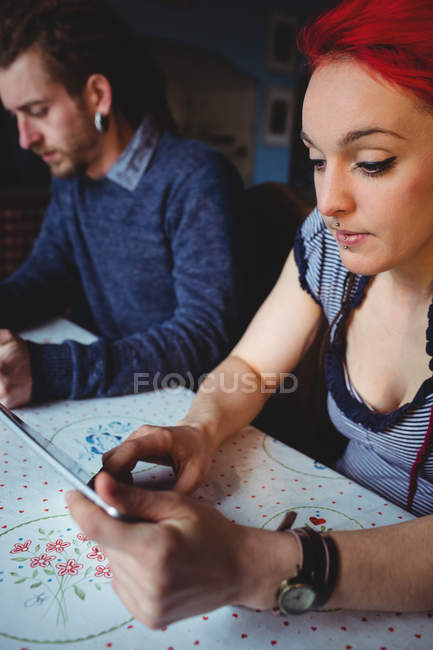 Beautiful woman using tablet while sitting by man at home — Stock Photo