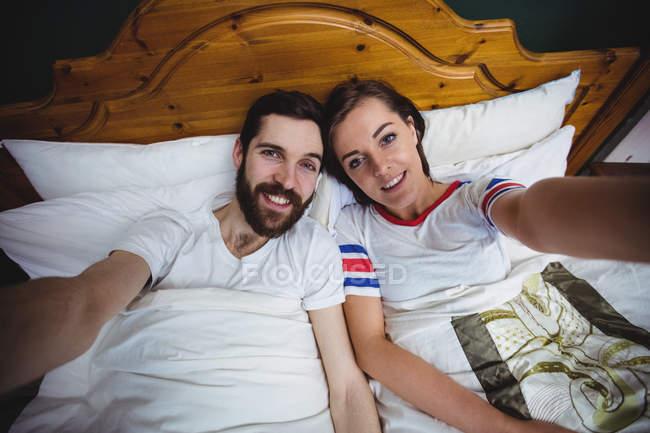 Portrait de couple couché ensemble sur le lit dans la chambre — Photo de stock
