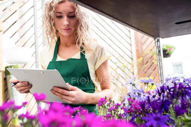 Female florist examining flowers in garden centre — Stock Photo