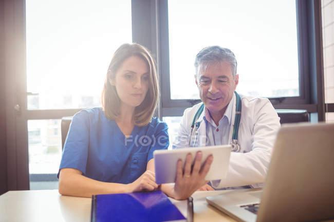 Médico discutindo com enfermeira sobre tablet digital no hospital — Fotografia de Stock