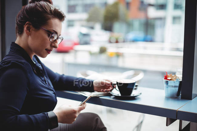 Young businesswoman using mobile phone in cafe — Stock Photo