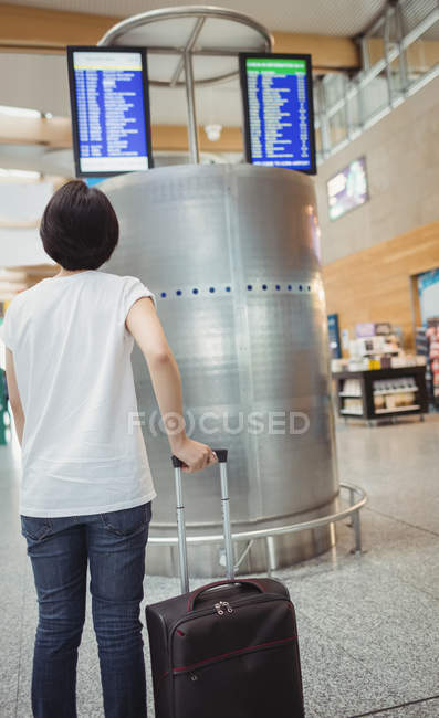 Woman looking at departure and arrival screen board displays in airport — Stock Photo
