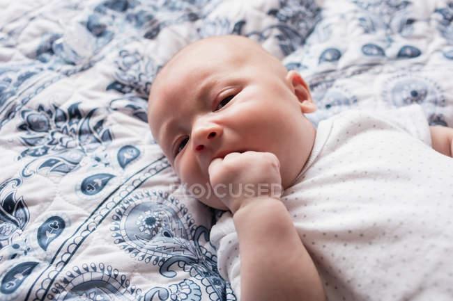 Bambino sdraiato sul letto in camera da letto a casa — Foto stock