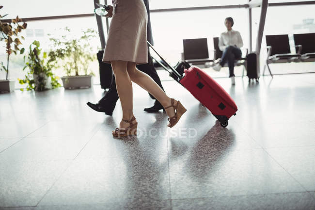 Business people walking with luggage in airport terminal — Stock Photo