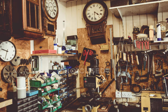 Old horologists workshop with clock repairing tools, equipment and clocks on the wall — Stock Photo