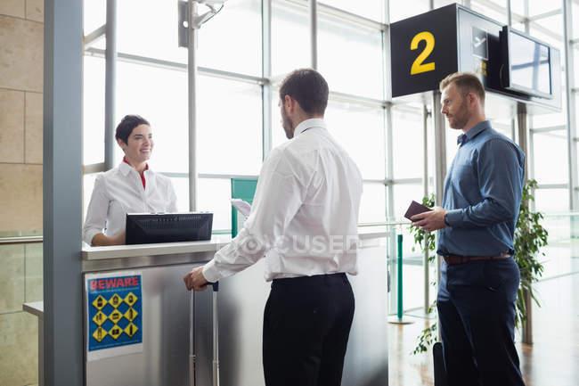 Mann gibt Flugbegleiterin am Flughafen-Check-in-Schalter seinen Reisepass — Stockfoto
