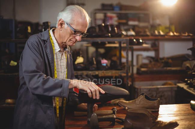 Shoemaker repairing a shoe in workshop — Stock Photo