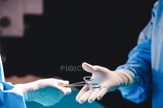 Hands of surgeon giving operation scissors to colleague in operation room at hospital — Stock Photo
