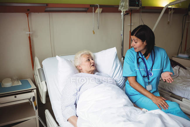 Nurse interacting with senior patient in hospital — Stock Photo