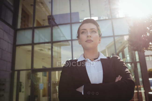 Confident businesswoman with arms crossed standing outside office building — Stock Photo