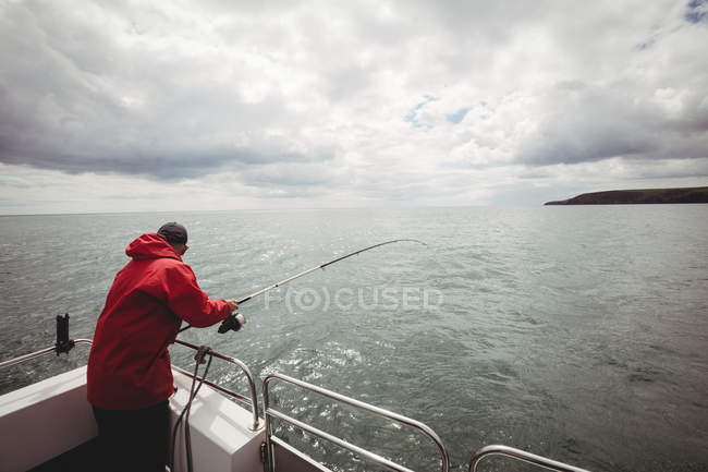 Back view of Fisherman fishing with fishing rod from boat — Stock Photo