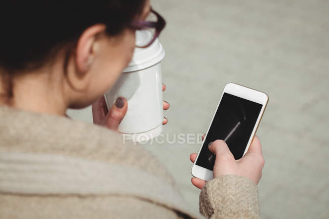 Woman using mobile phone while holding disposable coffee cup — Stock Photo
